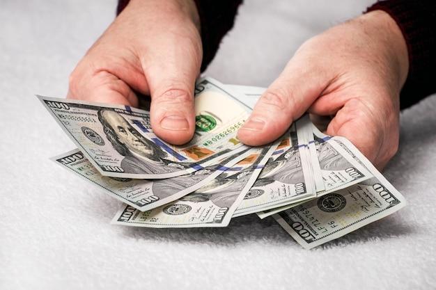 Мужчина держит доллары в руках. мужчина считает деньги