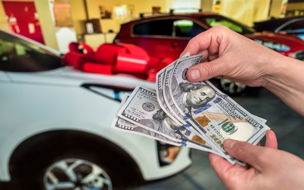 Man holding dollars for rent or buy car as background. business concept