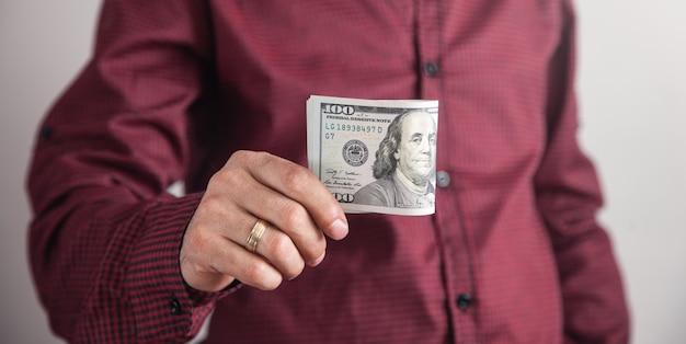 Мужчина держит доллары, стоя на сером фоне.