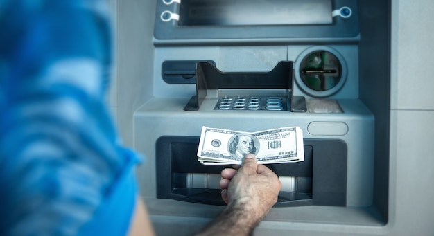 Man holding dollars withdrawn from atm.