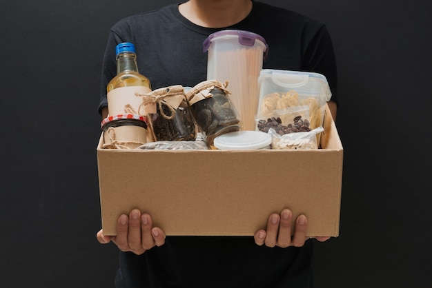 A man holding a donation box of different products on dark