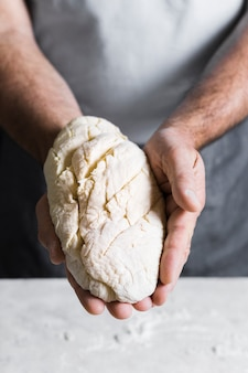 Man holding dough for bread front view