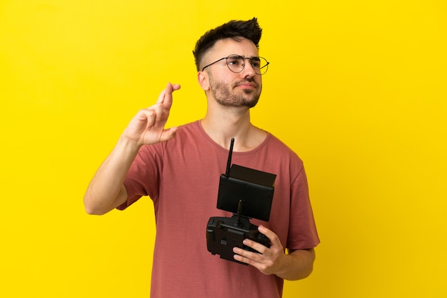 Man holding a drone remote control isolated on yellow background with fingers crossing and wishing the best