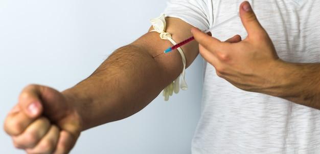 Man holding drug syringe injection