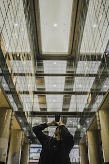 廊下で写真を撮っている間デジタル一眼レフカメラを持っている男