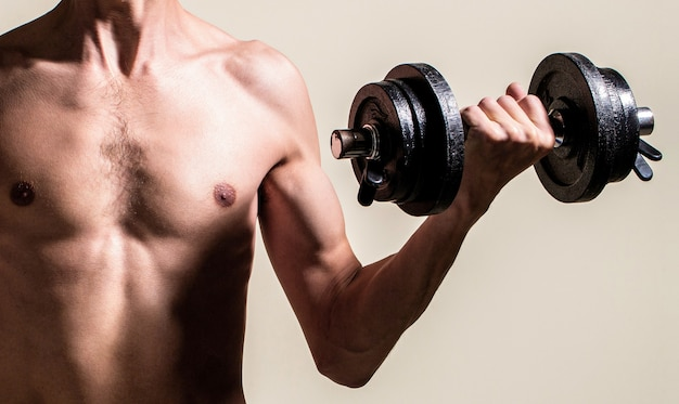 Man holding dumbbell in hand. skinny guy hold dumbbells up in hands. a thin man in sports with dumbbells