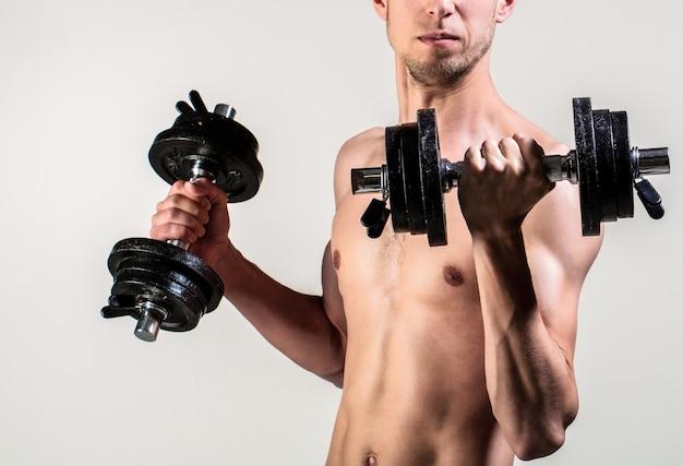 아령을 손에 들고 있는 남자. 마른 남자가 손에 아령을 들고 있습니다. 아령으로 스포츠에 마른 남자입니다. 약한 남자는 무게, 아령, 팔뚝, 근육, 피트니스를 들어 올립니다. 아령을 maleraising 괴상한입니다.
