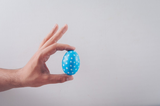 Man holding an easter egg on white background.