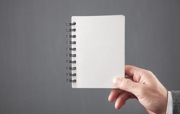 空のメモ帳を持っている男。あなたのテキストのためのスペース