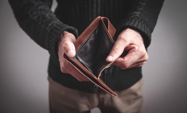 Мужчина держит пустой бумажник.