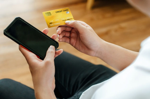 Мужчина держит вводящий код на мобильном телефоне и оплачивает счет кредитной картой на столе в домашнем офисе