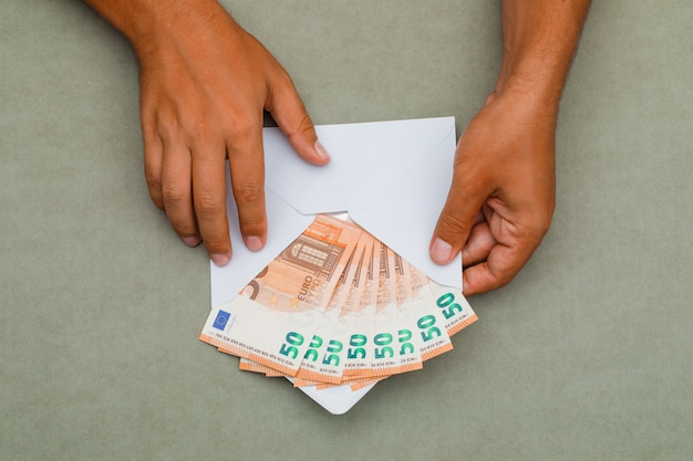 Мужчина держит конверт полный банкнот.