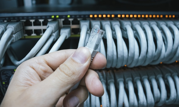 Man holding an ethernet cable ready for connection into the network switch.