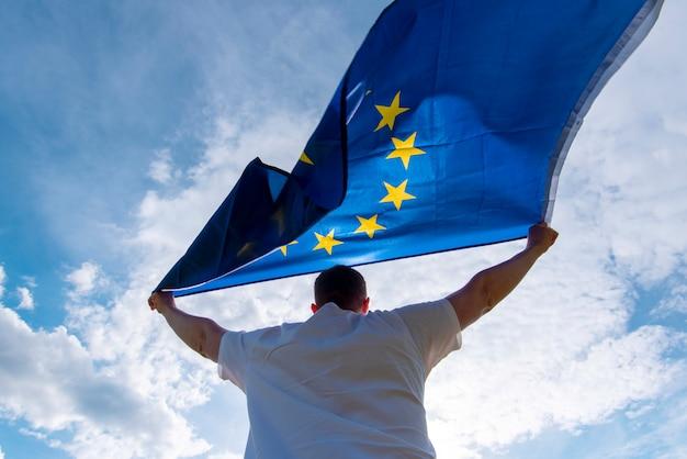 Мужчина держит флаг ес или флаг европейского союза, концепт картинки