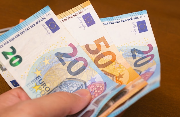 A man holding euro banknotes in his hand