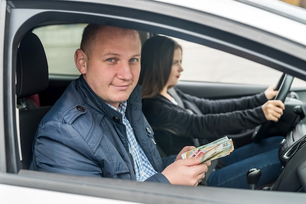 Мужчина держит банкноты евро, сидя в машине