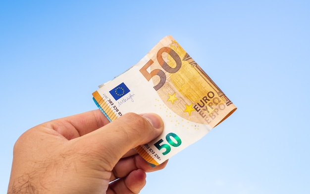 A man holding euro banknotes with blue sky background