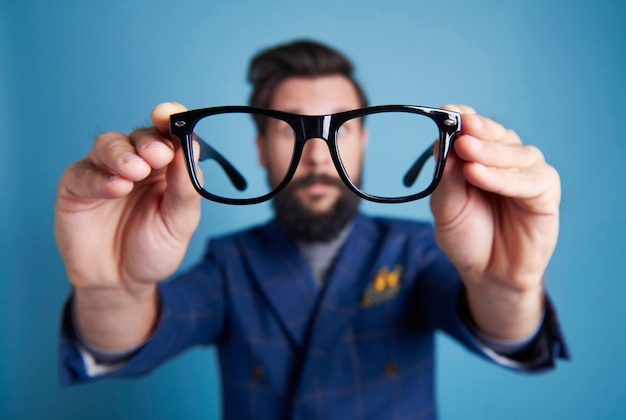 Uomo con gli occhiali davanti al viso