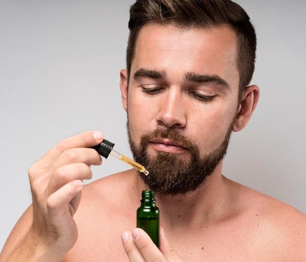 Uomo che tiene un primo piano della bottiglia di olio del fronte