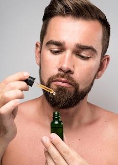 Uomo che tiene una bottiglia di olio per il viso