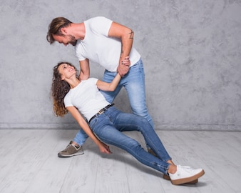 Man holding falling woman over floor