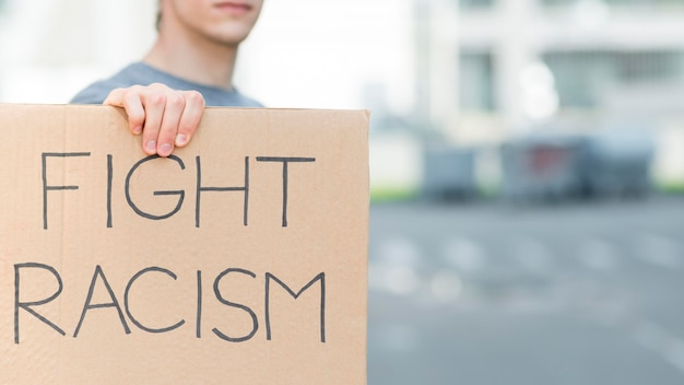 Man holding fight racism quote on cardboard copy space