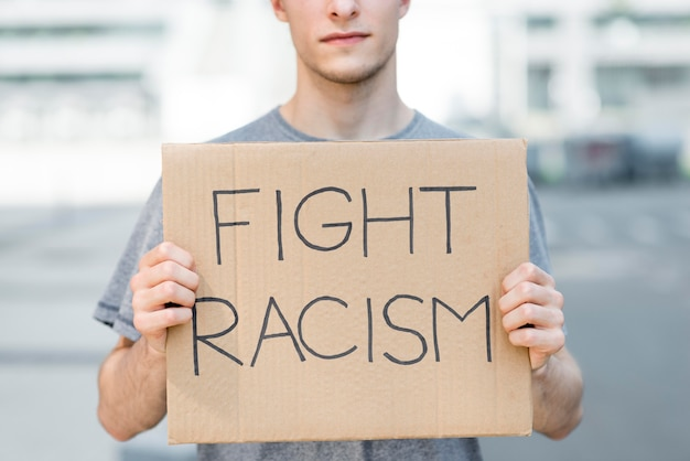 Man holding fight racism quote on cardboard