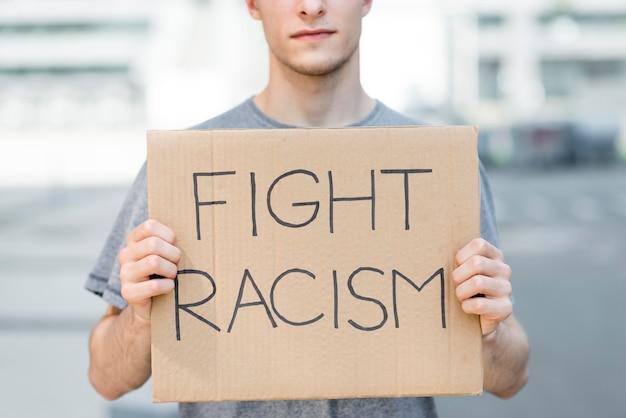段ボールに人種差別の見積もりを抱きかかえた