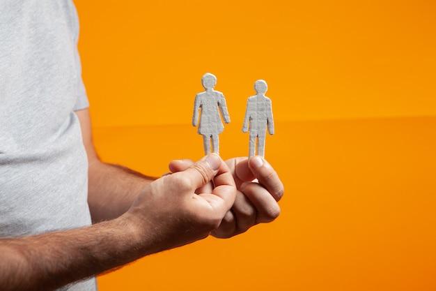 オレンジ色の背景に彼の手で人々の姿を保持している男