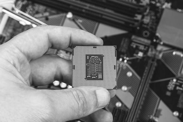 Мужчина держит пальцы настольного процессора 8-го поколения на фоне материнской платы крупным планом, вид сверху, черно-белое фото