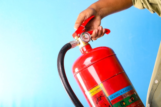 A man holding fire extinguisher on blue background.