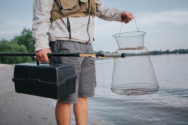 漁網とプラスチックのブラックボックスを手で保持している男。また、彼は右の1つで大胆に飛びました。ガイは、ワット海岸に立っています。