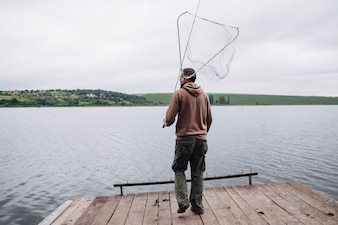 Man holding fishing net and rod standing on wooden pier in front of lake