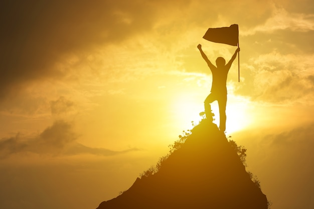 Man holding flag on the peak of mountain and sunset outdoor on nature