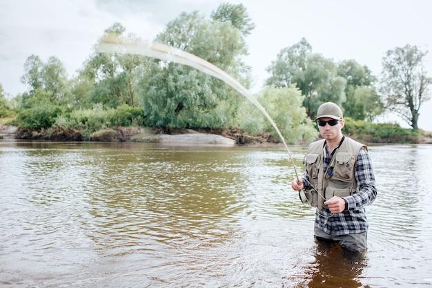 フライロッドを抱きかかえた。振動している。男はスプーンの一部を手に持っています。彼は水中に立っています。彼は真剣でクールに見えます。