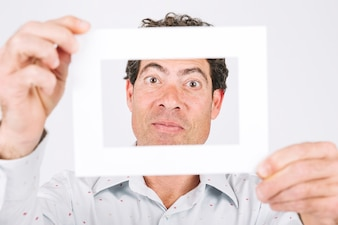 Man holding frame in front of his face