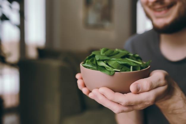Мужчина держит свежий зеленый салат, листья шпината