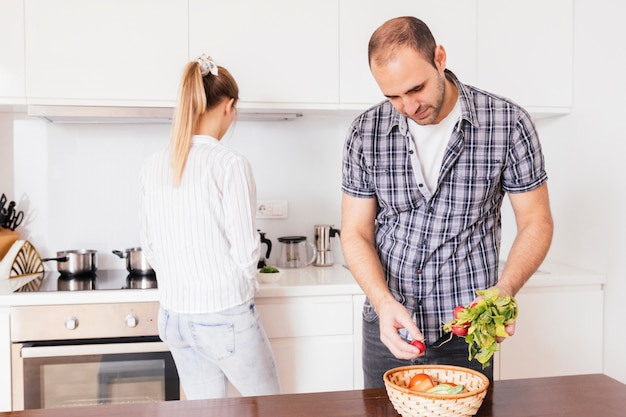 Man holding fresh healthy red radish with his girlfriend standing at background