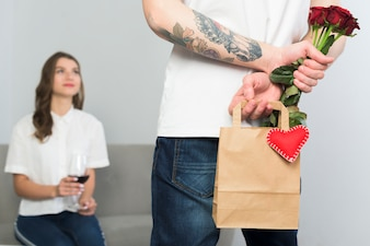 Man holding gift bag for woman behind back
