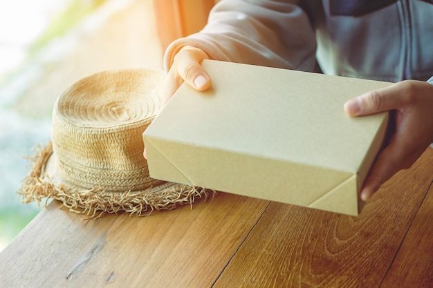 Man holding a gift box hat on a wooden table