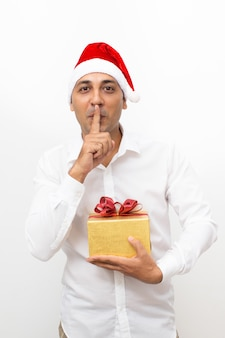 Man holding gift box and showing silence gesture