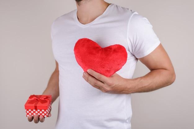 Мужчина держит подарочную коробку и красное сердце возле сундука