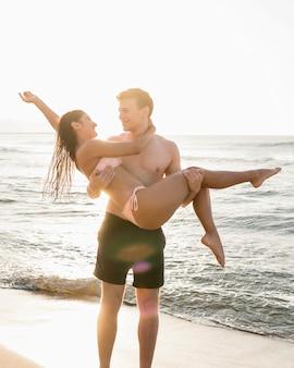 ビーチでガールフレンドを保持している男