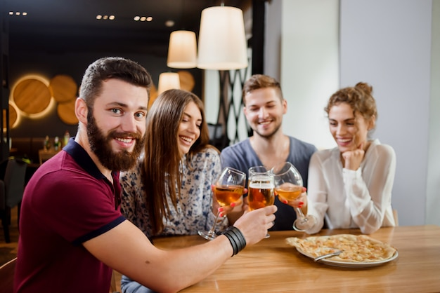 Man holding glass of beer and sitting in pizzeria with friends.