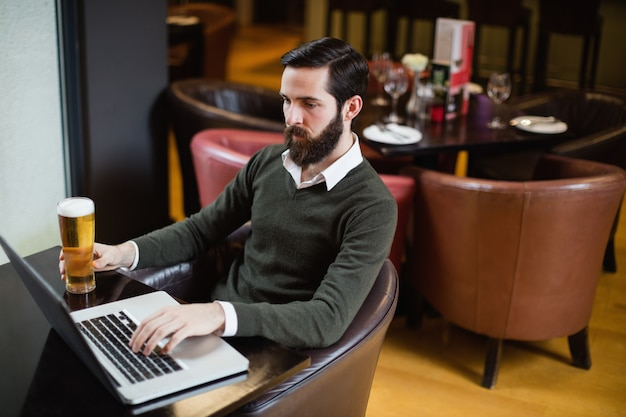 Man holding glass of beer and using laptop