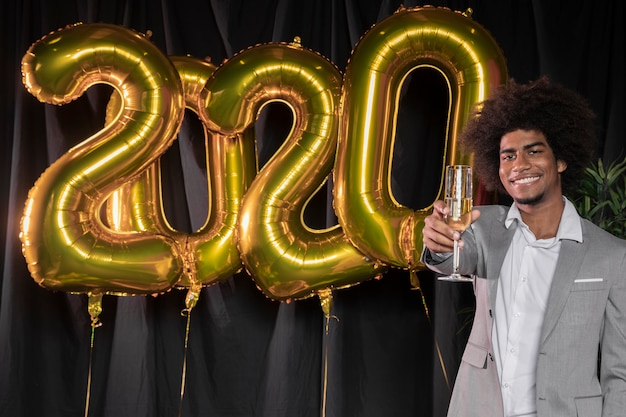 Man holding a glass of champagne and happy new year 2020 balloons