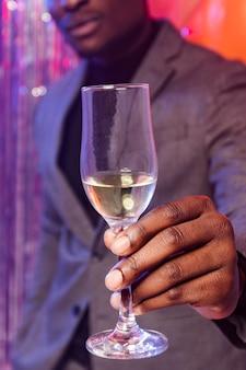 Uomo che tiene un bicchiere di champagne