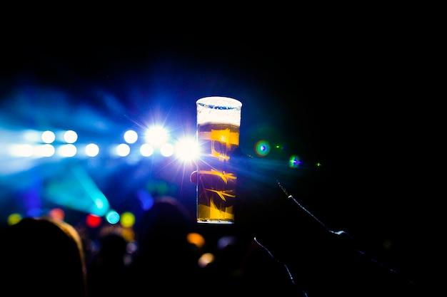 Человек, держащий стакан пива в ночной концерт. до неузнаваемости толпа фон. синие огни