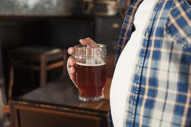パブで彼の大きな腹の近くにビールのガラスを保持している男