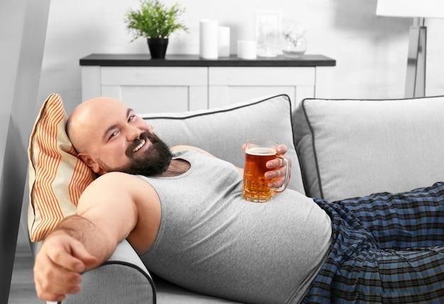 自宅で彼の大きな腹にビールのガラスを保持している男